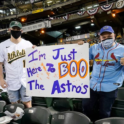 Fans pose with a sign against the Houston Astros during the game with the Oakland Athletics at RingCentral Coliseum on April 02, 2021 in Oakland, California.